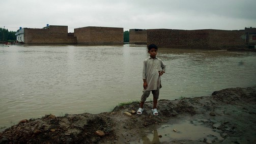 A boy stands in front of a flooded village in Charsadda, Pakistan
